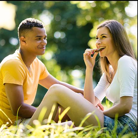 Couple sitting in field enjoying their homemade chocolate